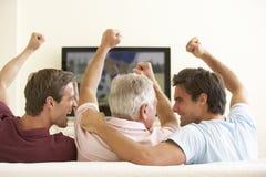 Tre uomini che guardano TV a grande schermo a casa Fotografia Stock Libera da Diritti