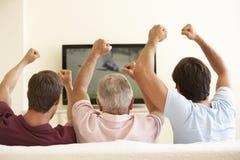 Tre uomini che guardano TV a grande schermo a casa Immagine Stock
