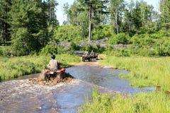 Tre uomini che guidano ATV quad attraverso l'acqua sporca in foresta fotografia stock libera da diritti