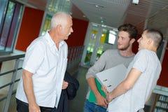 Tre uomini che hanno conversazione sul corridoio Immagine Stock