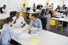 Tre uomini che lavorano insieme in un ufficio occupato, vista elevata fotografie stock