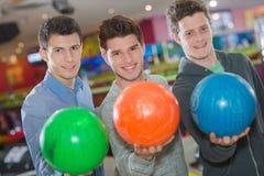 Tre uomini con le palle da bowling Immagini Stock