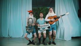 Tre uomini divertenti vestiti come dwarfes che giocano gli strumenti musicali sulla scena video d archivio