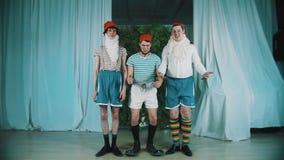 Tre uomini divertenti vestiti come gnomi saltano simultaneamente, sguardo alle mani sorprese stock footage