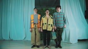 Tre uomini divertenti vestiti come lavoratori sporchi della strada saltano simultaneamente sulla scena archivi video