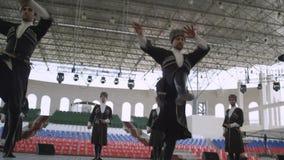 Tre uomini eseguono l'insieme delle gente della Inguscezia di salti di dancing stock footage