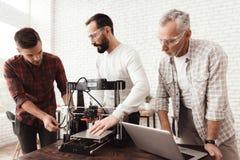 Tre uomini hanno installato una stampante fatta da sé 3d per stampare il pezzo in lavorazione Un uomo anziano con un computer por Fotografia Stock