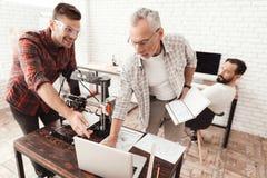 Tre uomini hanno installato una stampante fatta da sé 3d per stampare la forma Controllano il modello 3d sul computer portatile Immagine Stock Libera da Diritti