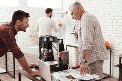 Tre uomini hanno installato una stampante fatta da sé 3d per stampare la forma Controllano il modello 3d sul computer portatile Fotografia Stock