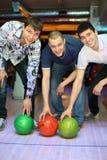 Tre uomini hanno piegato sopra per sollevare sulle sfere per il bowling Immagine Stock