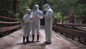 Tre uomini in rischio biologico è adatta alla condizione su un ponte fotografie stock