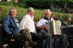 Tre uomini si siedono sul banco ed ascoltano musica - i climi di Kazimierz Dolny, Polonia, 06 2011 fotografie stock libere da diritti