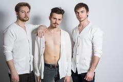 Tre uomini in un cardigan bianco sopra il suo corpo nudo immagini stock