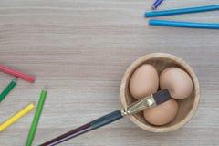 Tre uova in ciotola di legno con una spazzola e matite di colore su legno immagine stock