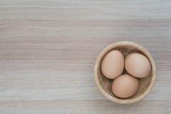 Tre uova in ciotola di legno su superficie di legno fotografie stock
