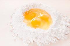 Tre uova crude in farina bene su legno (che produce la pasta della pasta dell'uovo) Immagini Stock Libere da Diritti