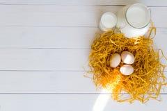 Tre uova del pollo nel nido decorativo con un lanciatore e un bicchiere di latte su fondo di legno bianco Immagini Stock Libere da Diritti