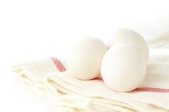 Tre uova del pollo su un panno di tela Immagini Stock Libere da Diritti