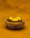 Tre uova di nido dell'oro Fotografie Stock