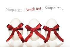 Tre uova di Pasqua bianche della caramella con i nastri rossi Fotografie Stock Libere da Diritti