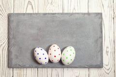 Tre uova di Pasqua dipinte su un piatto concreto su un fondo leggero immagine stock libera da diritti