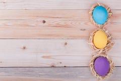 Tre uova di Pasqua in piccoli nidi su fondo di legno fotografie stock libere da diritti