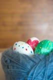 Tre uova di Pasqua si trovano in un groviglio di lana Fotografia Stock