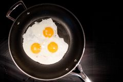 Tre uova fritte in una vaschetta di frittura fotografia stock libera da diritti