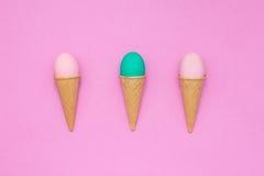Tre uova nei coni della cialda su un fondo rosa Fotografie Stock