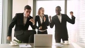 Tre upphetsade affärspersoner som dansar i arbetsplatsen som firar seger lager videofilmer