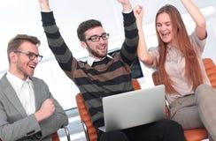Tre upphetsade anställda som tillsammans mottar goda nyheter på linje Royaltyfri Fotografi