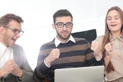 Tre upphetsade anställda som tillsammans mottar goda nyheter på linje Arkivfoto