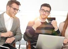 Tre upphetsade anställda som tillsammans mottar goda nyheter på linje Arkivbild