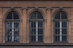Tre välvda fönster på en gammal utsmyckad fasad fotografering för bildbyråer