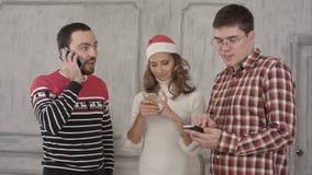 Tre vänner använder deras mobiltelefoner på en vit stock video