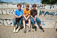 Tre vänner kopplar av från skateboardkörning royaltyfri bild
