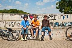 Tre vänner kopplar av från skateboardkörning royaltyfria foton