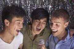 Tre vänner med armen runt om de som rymmer en mikrofon och tillsammans sjunger på karaoke arkivbilder