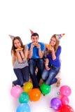 Tre vänner med hattar och ballonger som äter pizza Arkivbilder