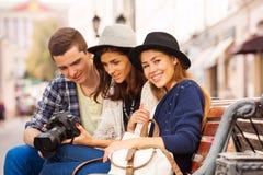 Tre vänner med kameran sitter tillsammans på bänk Royaltyfria Bilder