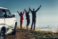 Tre vänner sammanfogade händer och lyftte upp deras händer och att tycka om sikten av utomhus- Semesterresabegrepp royaltyfri foto