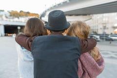 Tre vänner, sikt från baksidan av den unga tonåringpojken som kramar två flickor vid skuldrorna Barn ser framåt, stadsliv arkivbild