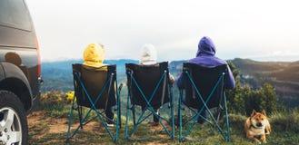Tre vänner sitter i campa stolar överst av ett berg, handelsresande tycker om naturen och kopplar av, turister med hundblick in i royaltyfria bilder