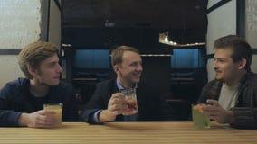 Tre vänner sitter i en stång som kopplar av och talar med de arkivfilmer