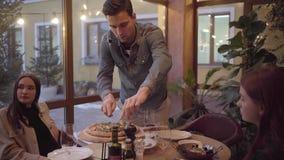 Tre vänner som äter smaklig pizza och dricker vin i modernt italienskt kafé på tabellen Två unga kvinnor och en man har stock video