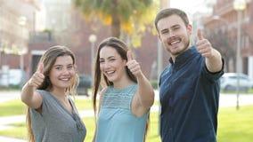 Tre vänner som gör en gest upp tummen på kameran arkivfilmer