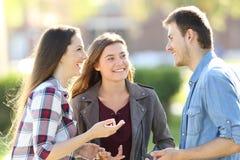 Tre vänner som har en konversation i gatan royaltyfria bilder