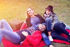 Tre vänner som har en picknick och tycker om solen Royaltyfri Fotografi
