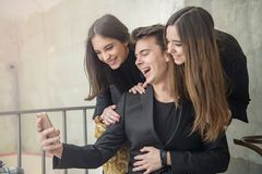 Tre vänner som har gyckel i ett kafé royaltyfria bilder