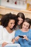 Tre vänner som läser ett textmeddelande arkivfoton